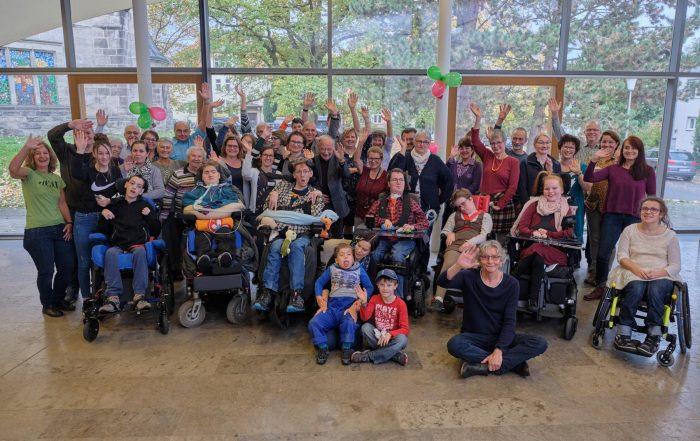 Treffen-mit-Intensivkindern:-Zum-Gruppenfoto-mit-Eltern-Intensivpflegekindern-und-Musikern-sie-alle-sind-zusammengeschlossen-im-verein-intensiv-leben-kassel-e.V.-und-gaben-Reporter-Thomas-Pfundtner-einen-Einblick-in-ihr-Leben.-er-sitzt-am-boden-vor-der-großen-Gruppe