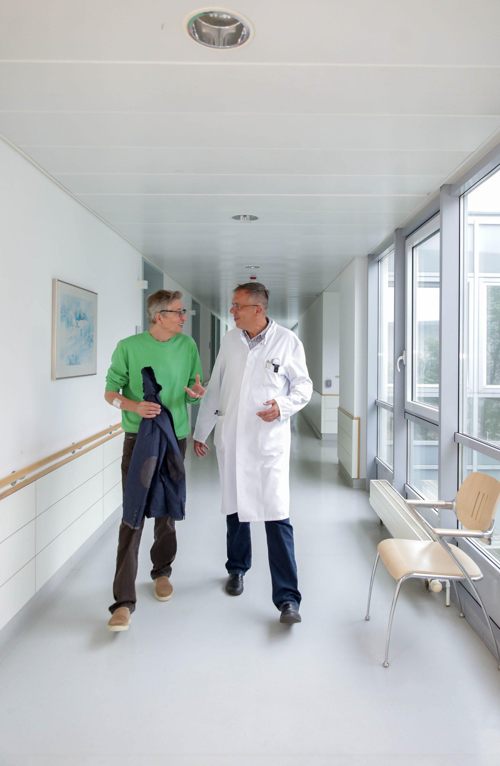 Diskutieren-lebhaft-auf-einem-Gang-ueber-den-Reha-Verlauf:Chefarzt-Doktor-Ron-Lenz-und-Thomas-Pfundtner-Der-Arzt-mit weißem-Kittel-Thomas-Pfundtner-in-brauner-Jeans-und-gruenme-Pullover