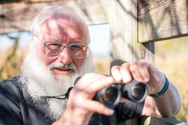 Ornithologe-Peter-Berthold-mit-Fernglas-beobchatet-die-Vogelwelt-in Billafingen an der Feldstation am Heinz-Siemann-Weiher.