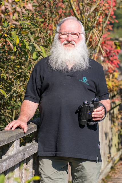 Portrait-des-Ornithologen-Peter-Berthold, der-einen-langen-weißen-Bart-trägt-ein-blaues-T-Shirt-anhat-und-in-der linken-Hand-ein-Fernglas-haelt-mit-Fernglas