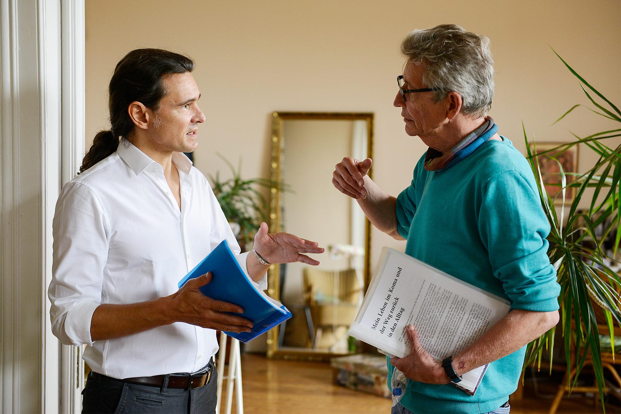 Dr-Tobias-Leis-im-Gespräch-mit-seinem-Patienten-Thomas-Pfundtner-nachdem-dieser-wieder-fit-war-Gemeinsam-studieren-die-beiden-die-Patientenunterlagen