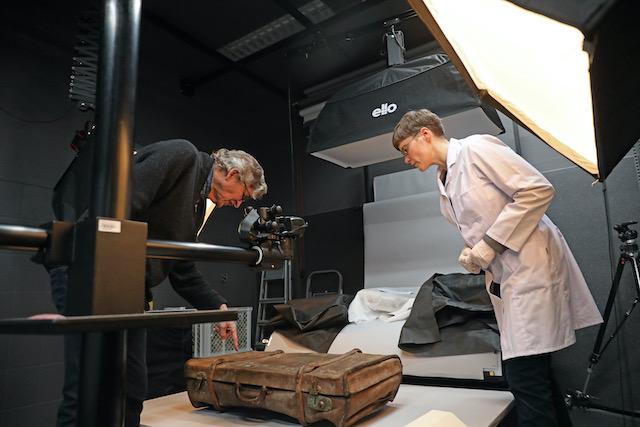 Im-fotostudio-erklaert-Margrit-borrmann-dem-reporter-thomas-pfundtner-was-am-beginn-einer-jeden-konservierung-steht-fotoaufnahmen-des-obkjekts-hier ein-alter-braune-lederkoffer-der-sehr-zerknautscht-aussieht