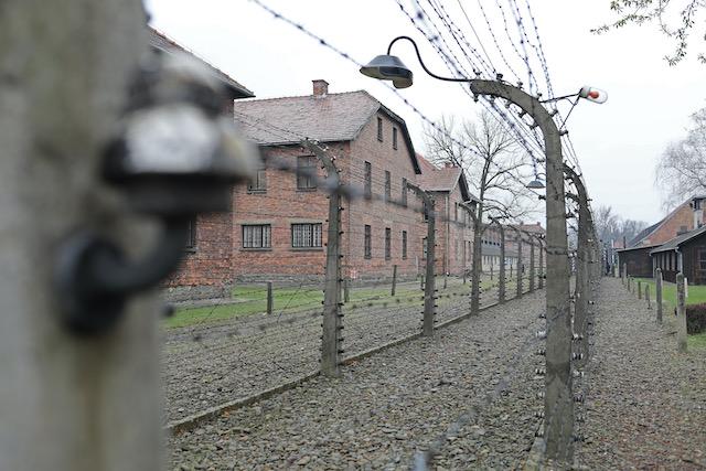 Blick-in-das-ehemalige-KZ-Auschwitz-links-baracken-des-lagers-umgeben-von-maschendrahtzaeunen-die-unter-strom-gesetzt-waren-es-sind-zwei-elektrozäaeune-die-diebaracken-von-anderen-gebaeuden-abtrennen-zwischen-den-monstern-aus-maschendraht-verlaeuft-ein-gang-für-die-waechter