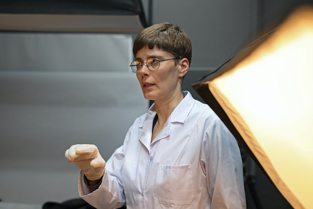 Margritt-borrmann-trägt-bei-ihrer-Arbeit-immer-einen-weißen-kittel-und-plastik-handschuhe-im-fotostudio-muss-sie-bevor-sie-einen-zu-konservierenden-gegenstand-ablichtet-zunächst-das objekt-ausleuchten-und-dann-genau-mittels-eines-protokolle-schriftlich-beschreiben