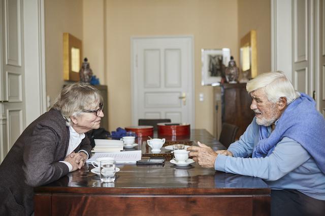 Beim-Interview-sitzt-Schauspieler-Mario-Adorf-an-dem-alten-aus-teakholz-gefertigten-Esstisch-rechts-auf-der-linken-seite-Interviewer-thomas-pfundtner-vor-dem-reporter-und-dem-kuenstler-stehen-kaffeetassen-laechelnd-hoert-sich-der-reporter-einne-antwort-von-mario-adorf-an-der-seinem-gegenüber-fest-in-die-augen-blickt