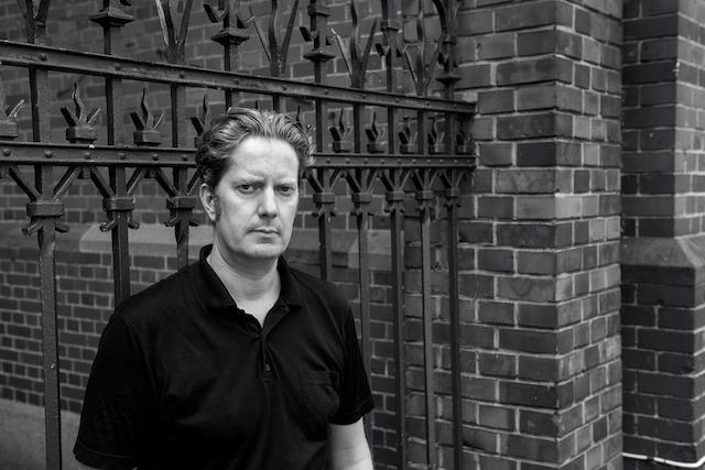 Watch-Autor-Michael-Meisheit-vor-einem-Stahlzaun