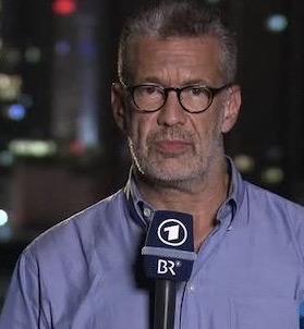 So-kennen-millionen-fernzuschauer-richard-c-schneider-der-reporter-haelt-ein-mikrofon-in-der-hand-und-berichtet-im-naechtlichen-Tel-Aviv-ueber-ereignisse-in-israel